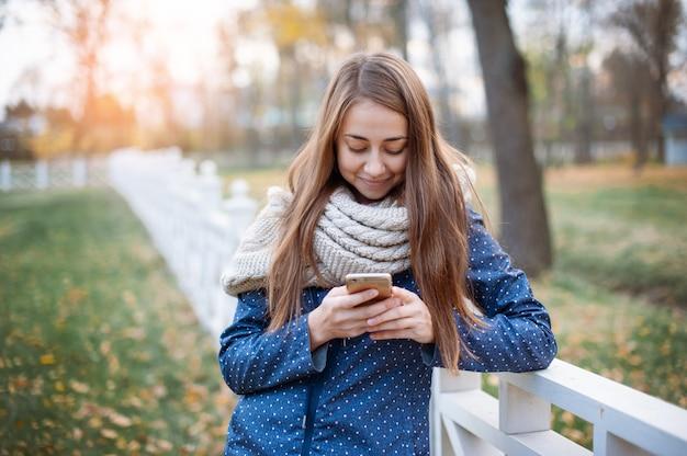 Jovem mulher feliz que usa um telefone esperto durante a caminhada no parque da cidade do outono.