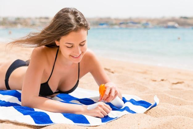 Jovem mulher feliz repousa sobre a toalha perto do mar e protege a pele das mãos com protetor solar do spray.