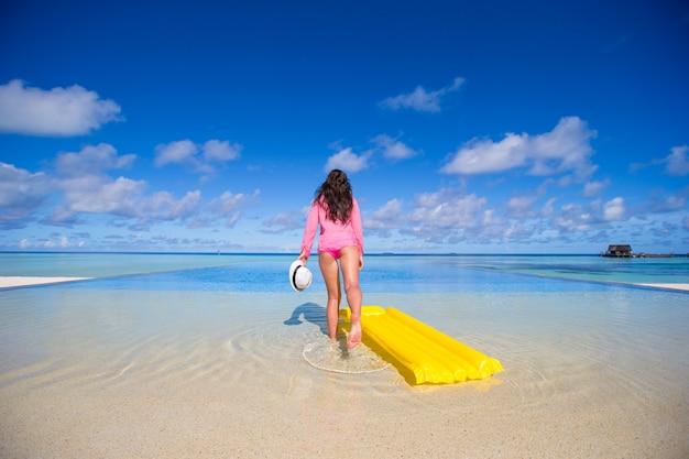Jovem mulher feliz se divertir com colchão de ar na piscina