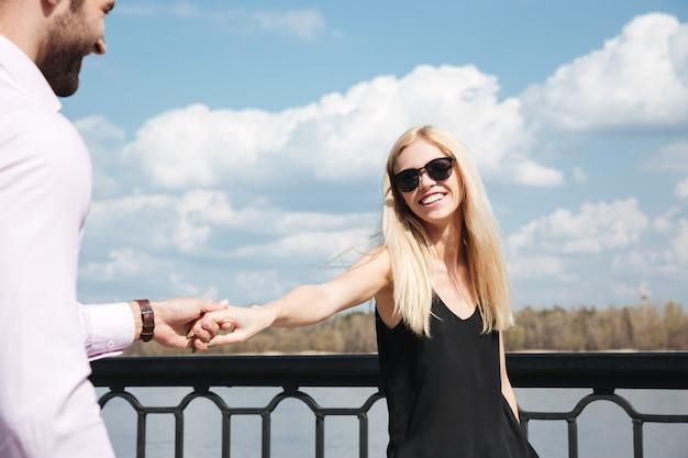 Jovem mulher feliz, segurando a mão do homem enquanto caminhava