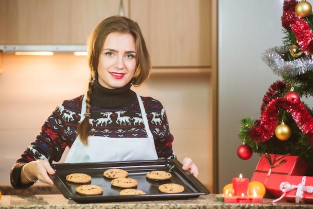 Jovem mulher feliz segurando assados biscoitos de chocolate perto da árvore de natal