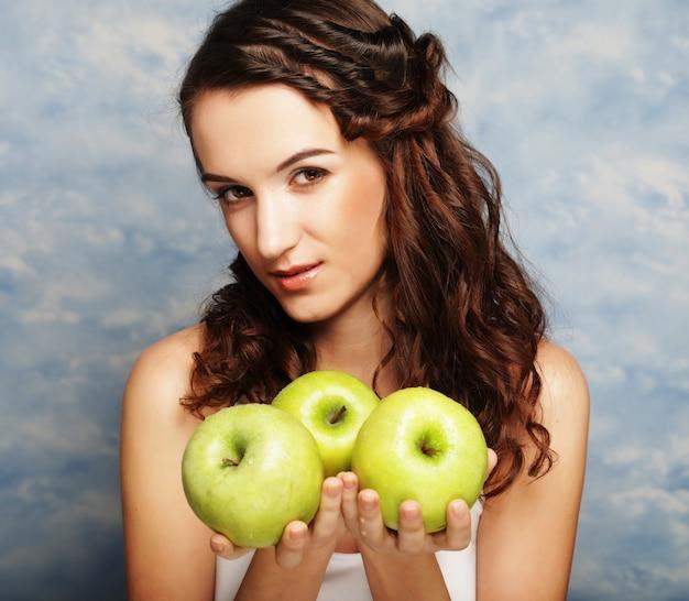 Jovem mulher feliz segurando maçãs verdes.