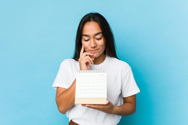 Jovem mulher feliz segurando um calendário