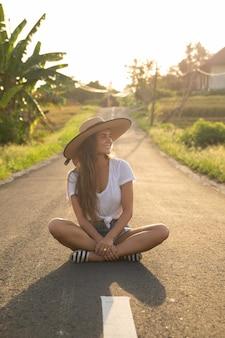Jovem mulher feliz sentada no meio da estrada de asfalto