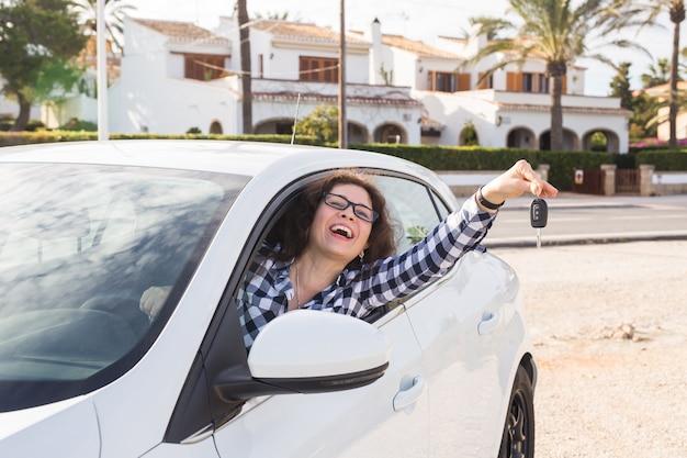 Jovem mulher feliz testando carro novo e mostrando a chave