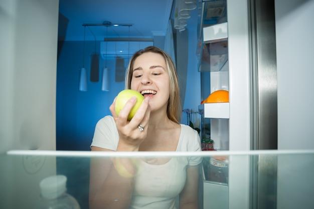 Jovem mulher feliz tirando maçã verde da geladeira
