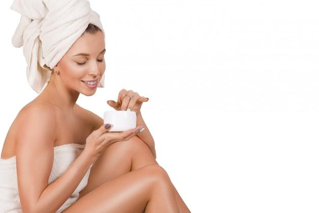 Jovem mulher feliz toalha aplicar creme na perna dela. conceito de cuidados com a pele