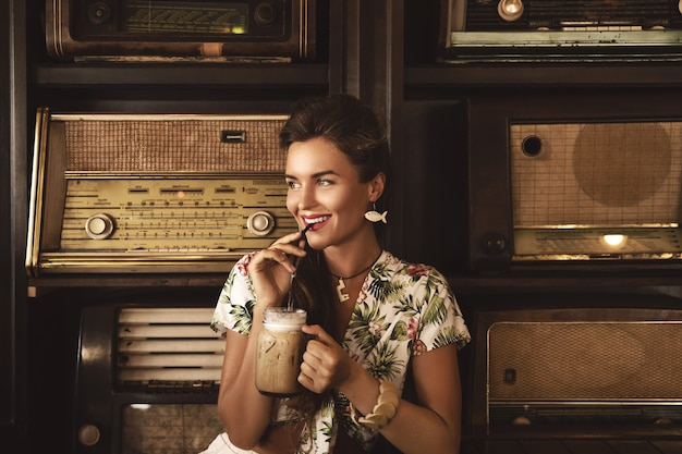 Jovem mulher feliz tomando café gelado em um elegante café retrô com um monte de rádios antigos