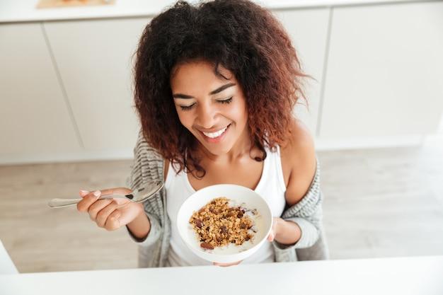Jovem mulher feliz tomando café na cozinha