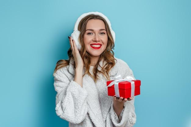 Jovem mulher feliz vestindo um casaco de pele branco artificial, sorrindo e segurando uma caixa de presente vermelha nas mãos e mostrando-a para a câmera isolada na parede azul. conceito de presentes de ano novo