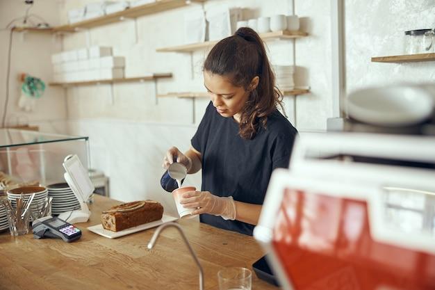Jovem mulher feminina barista derramando leite fresco para preparar café com leite para o cliente no café.