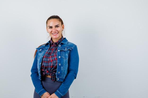 Jovem mulher feminina com camisa quadriculada, jaqueta, calça e parecendo alegre. vista frontal.