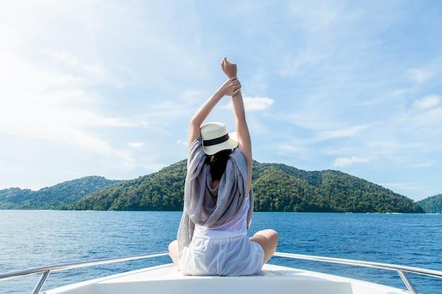 Jovem mulher férias relaxantes no barco e olhando mar perfeito