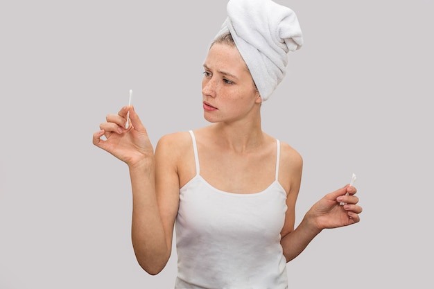 Jovem mulher fica e mantém varas de orelha nas mãos.