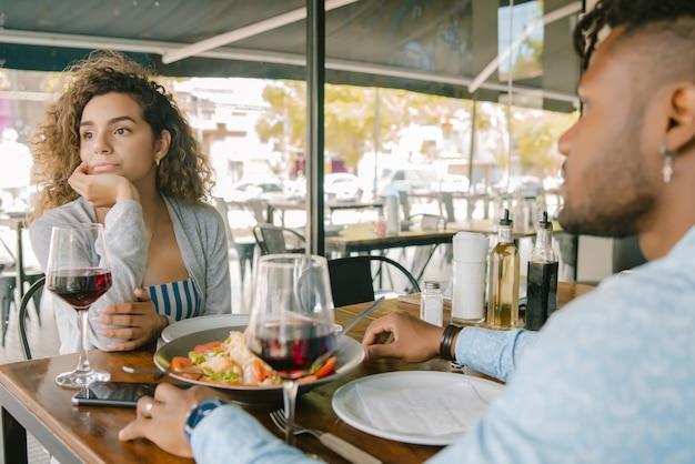 Jovem mulher ficando entediada em um almoço com um homem em um restaurante. conceito de relacionamento.