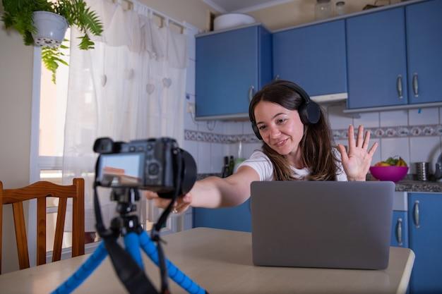 Jovem mulher filma um vídeo com sua câmera de vídeo enquanto usa o computador e usa fones de ouvido, blogger, rede social influenciadora feminina em casa - conceito de mulher freelance milenar tecnológica.