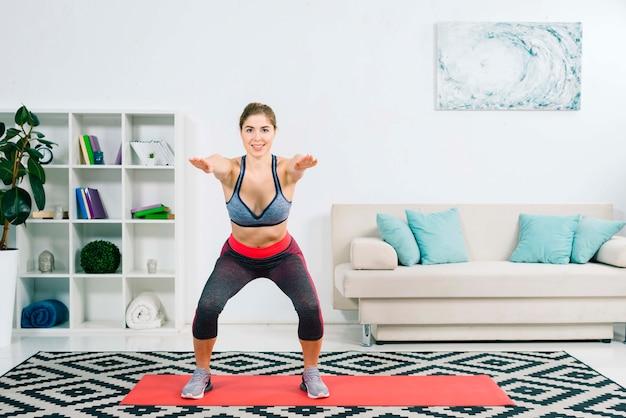 Jovem mulher flexível da aptidão que estica no tapete na sala de visitas moderna