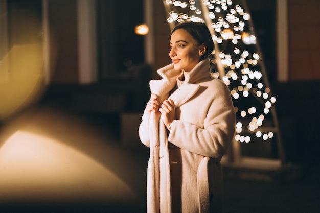 Jovem mulher fora da rua à noite com luzes