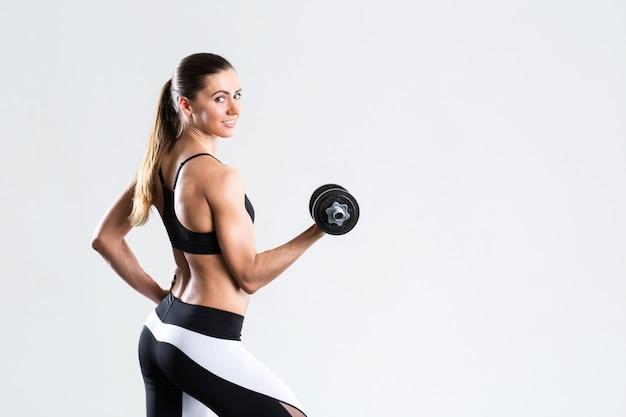 Jovem mulher forte do ajuste com o peso isolado.