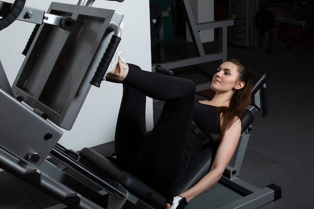Jovem mulher forte e esportiva fazendo exercícios de leg press na academia
