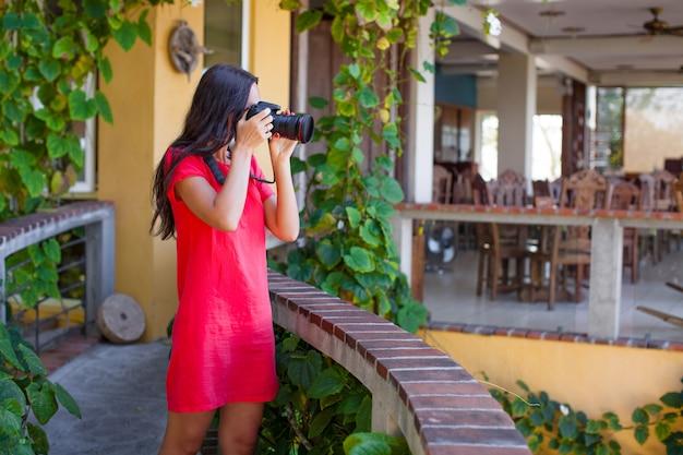 Jovem mulher fotografa a vista deslumbrante da varanda aconchegante