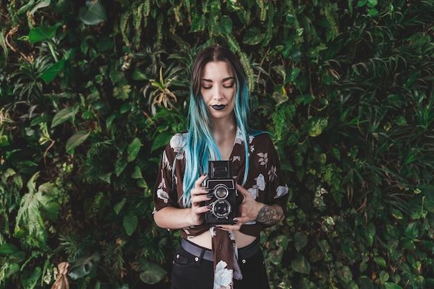 Jovem mulher fotografando com câmera vintage a sorrir