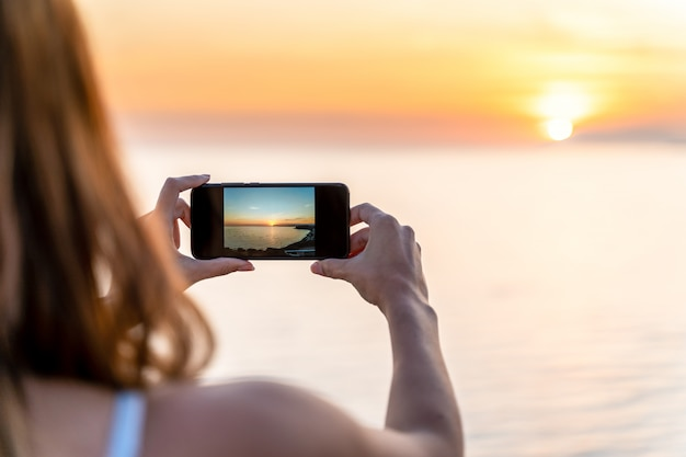 Jovem mulher fotografando um pôr do sol na praia com seu telefone celular