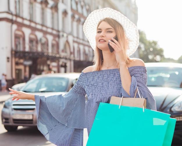 Jovem mulher gesticula para pegar um carro e falando ao telefone na estrada na cidade. carona conceito