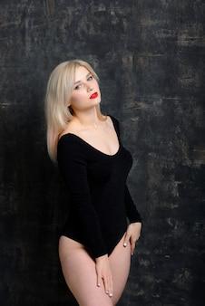 Jovem mulher gorda com maquiagem brilhante em traje preto está posando na parede escura, isolada.