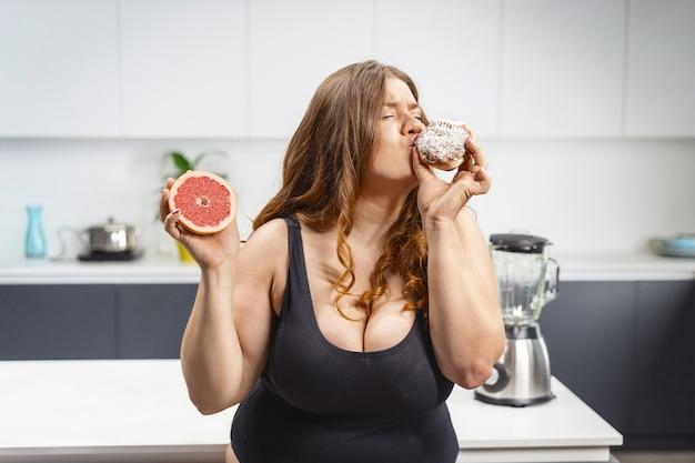 Jovem mulher gorda escolhendo o que comer segurando um bolo e uma toranja. mulher jovem e bonita gordinha comendo alimentos pouco saudáveis.
