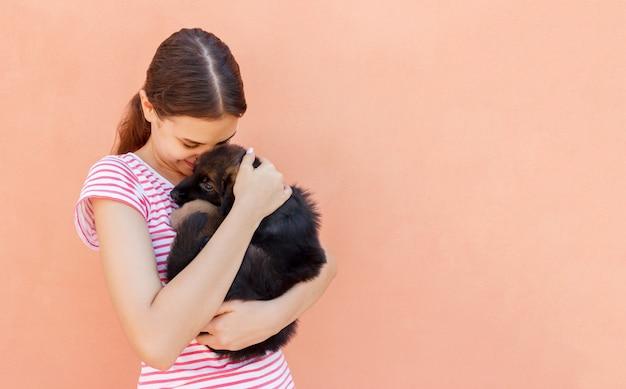 Jovem mulher gosta de abraçar um pequeno cachorrinho fofo