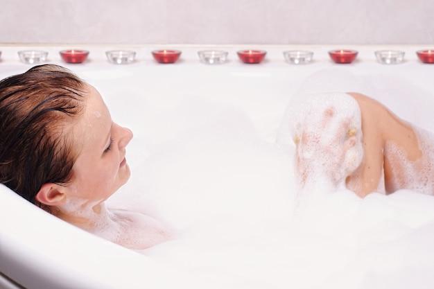 Jovem mulher gosta de banho-espuma na banheira.