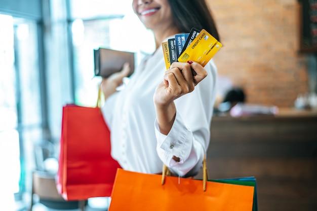 Jovem mulher gosta de fazer compras com cartões de crédito.