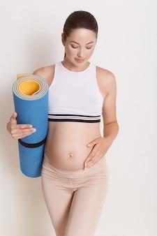 Jovem mulher grávida atraente tocando sua barriga, mantendo o tapete de ioga nas mãos Foto Premium