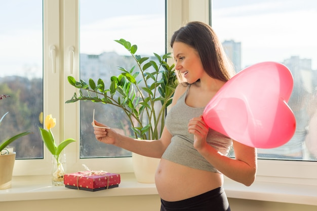 Jovem mulher grávida bonita com caixa de presente e coração de balão