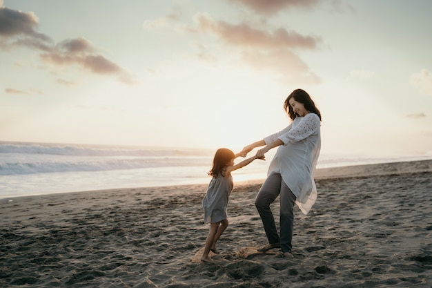 Jovem mulher grávida bonita com sua filha bonita brincando na praia