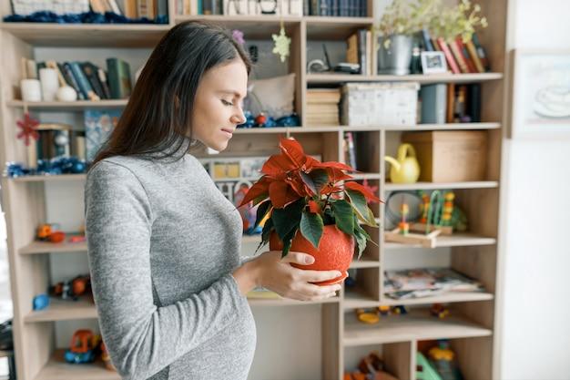 Jovem mulher grávida bonita com vermelho poinsétia de flores de natal
