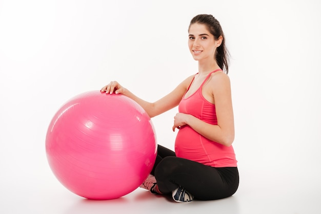 Jovem mulher grávida bonita fazendo exercícios com fitball