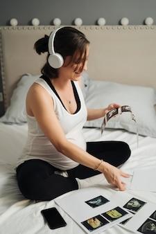 Jovem mulher grávida bonita ouvindo música com fones de ouvido enquanto revia os ultrassons do bebê sentado em sua cama no quarto dela