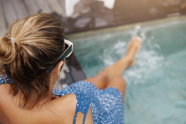 Jovem mulher grávida com nó de cabelo e pele bronzeada, sentada na beira da piscina e espirrando água nas pernas.