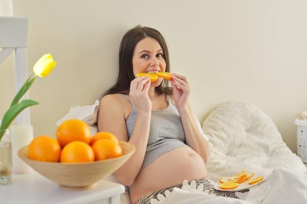 Jovem mulher grávida comendo laranjas em casa sentada na cama. vitaminas naturais, alimentos saudáveis, nutrição para mulheres grávidas