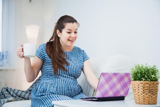 Jovem mulher grávida, compras on-line no laptop