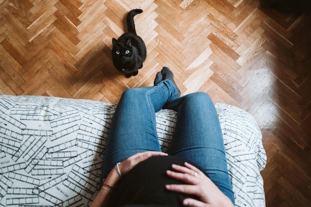 Jovem mulher grávida em casa. lindo gato preto além