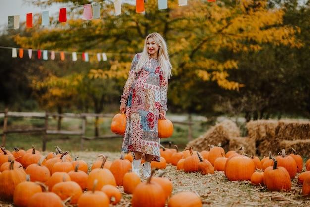 Jovem mulher grávida em vestido longo posando no campo de uma abóbora. fundo de outono