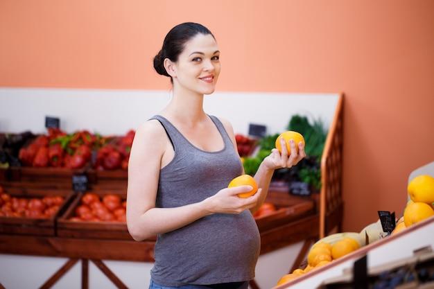 Jovem mulher grávida escolhe laranjas em uma loja de vegetais
