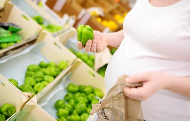 Jovem mulher grávida escolhendo frutas e legumes na sacola de compras de malha no supermercado