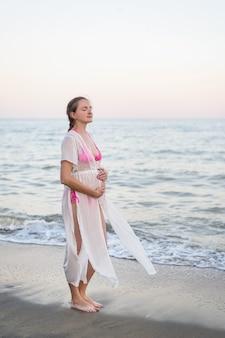 Jovem mulher grávida está de pé à beira-mar. abraçando a barriga e os olhos fechados. aproveitando o momento.
