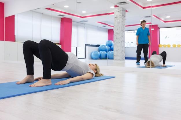 Jovem mulher grávida fazendo abdominais no chão