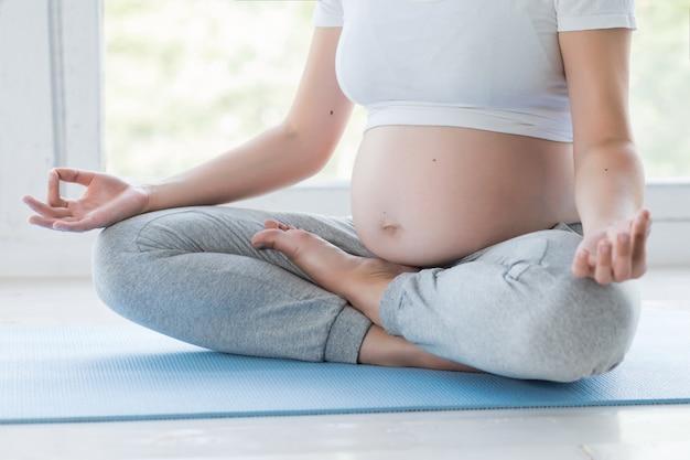 Jovem mulher grávida fazendo exercícios de fitness