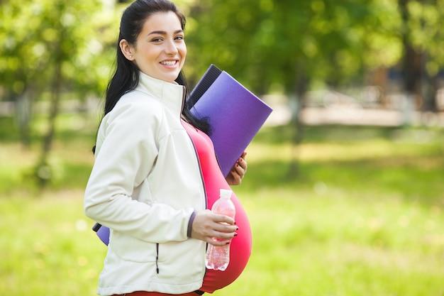 Jovem mulher grávida fazendo exercícios de ioga.